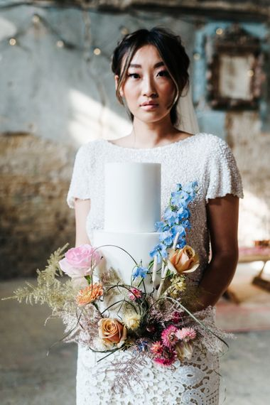 Bride holding a white iced wedding cake decorated with colourful flowers