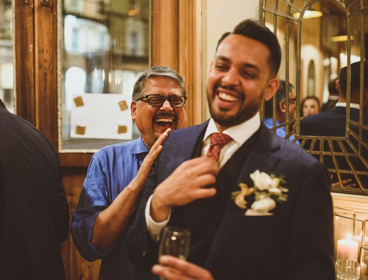 Groom laughing at wedding reception with red tie