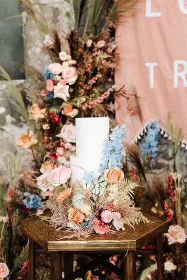 用五颜六色的结婚花装饰的白色结婚蛋糕