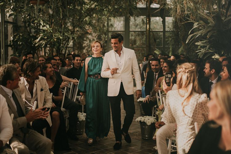 Groom walking down the aisle in a white dinner jacket