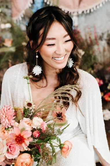 Beautiful bride with long earrings holding a colourful bouquet