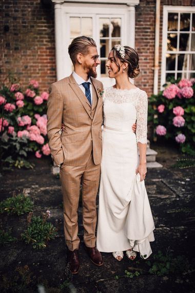 Bride in lace Sassi Holford wedding dress and groom in brown check suit