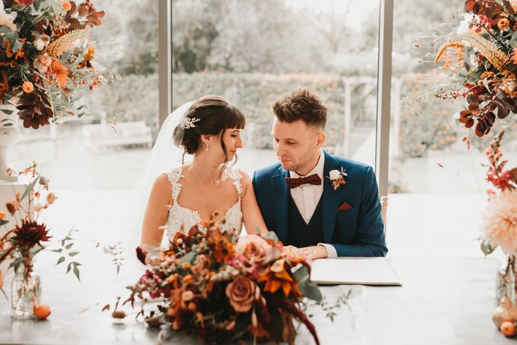 Bride and groom signing the register with autumn flowers