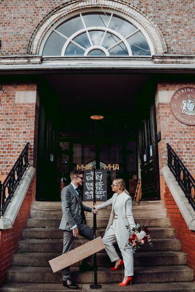 新娘穿着马西莫·杜蒂连衣裤配红鞋,新郎穿着灰色格子西装,由乔安妮·劳伦斯摄影公司设计188金宝博亚洲