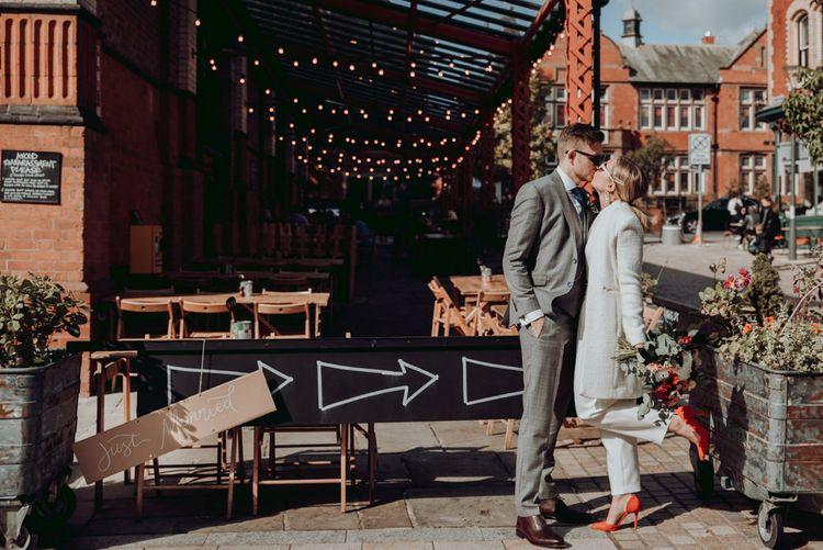 新娘穿着马西莫·杜蒂连衣裤和象牙色外套,新郎穿着灰色格子西装接吻