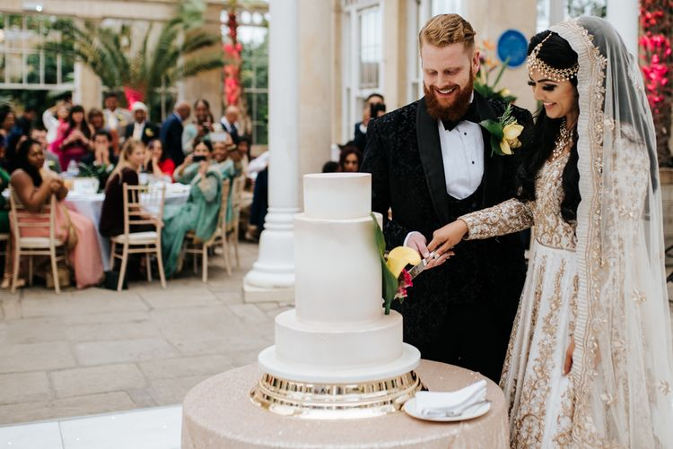 Bride and groom cutting the wedding cake at Syon Park reception