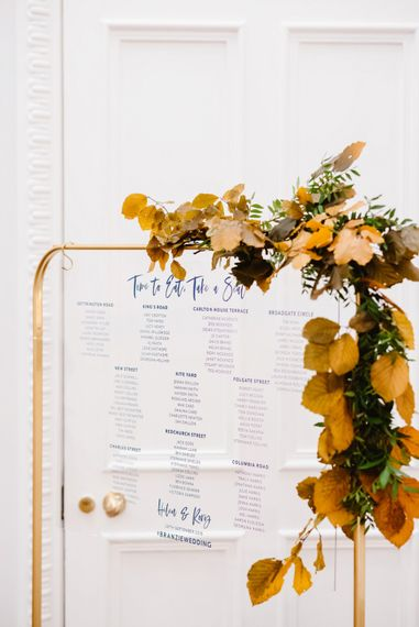 Acrylic seating chart on a gold frame with autumn flowers decorating