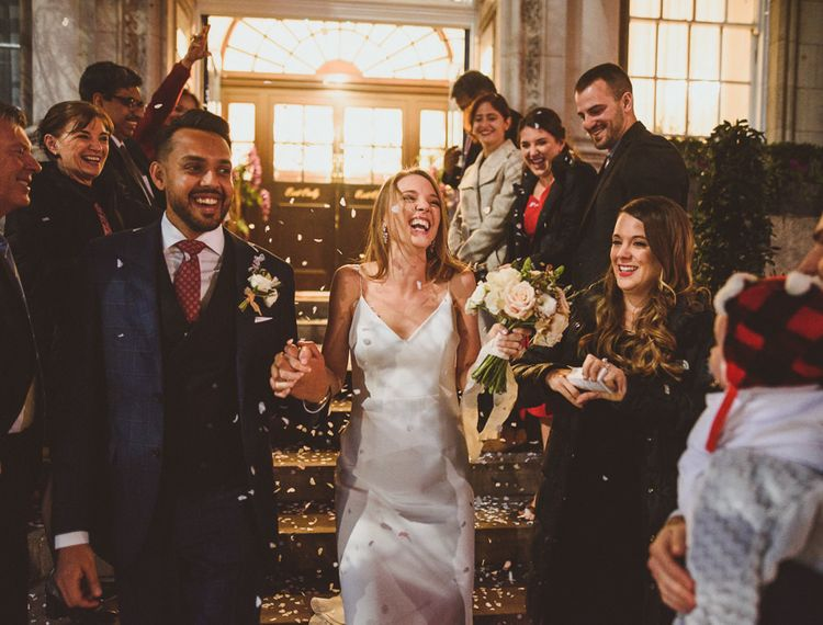 Bride laughing during confetti moment at London wedding
