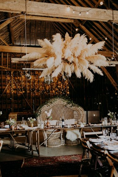 Top table with pampas grass installation and peacock chair love seat