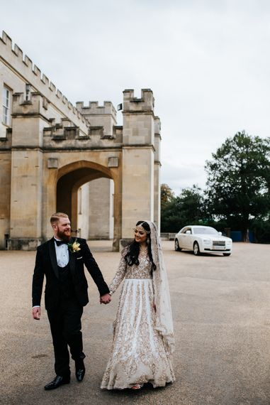 Indian bride in ivory and gold bespoke dress and groom in black tuxedo for fusion wedding