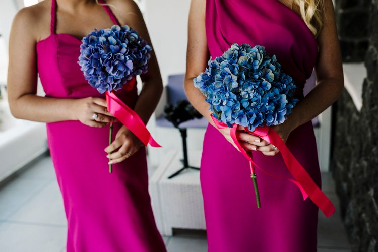 Bright pink bridesmaid dresses and blue hydrangea bouquets