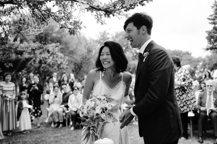 Black and white portrait of the bride and groom laughing during the outdoor wedding ceremony