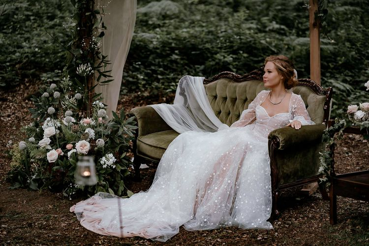 Bride in bespoke wedding dress sitting in the woods