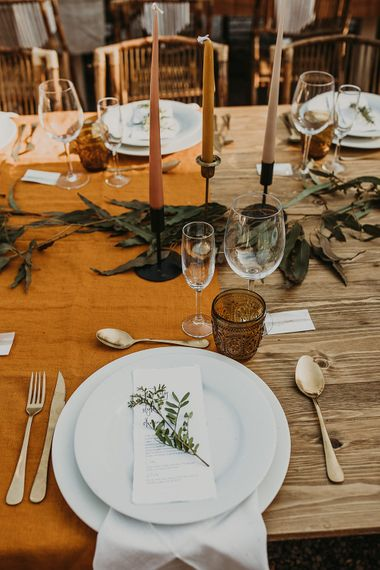 Place setting with coloured taper candles and olive branches