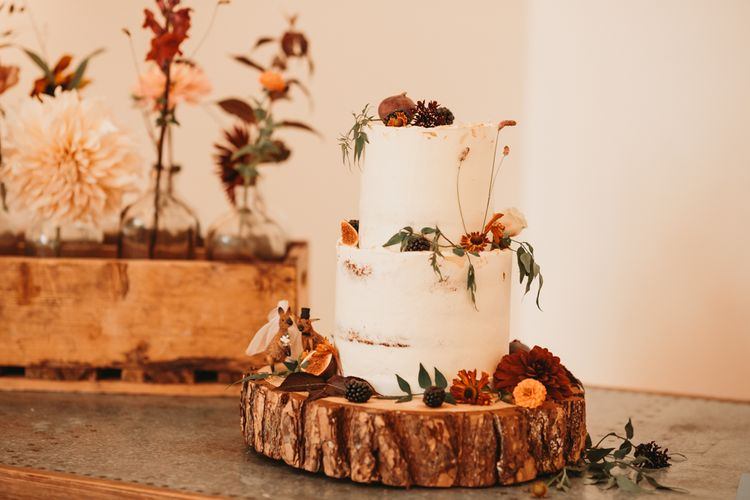 Rustic semi naked wedding cake on tree stump cake stand