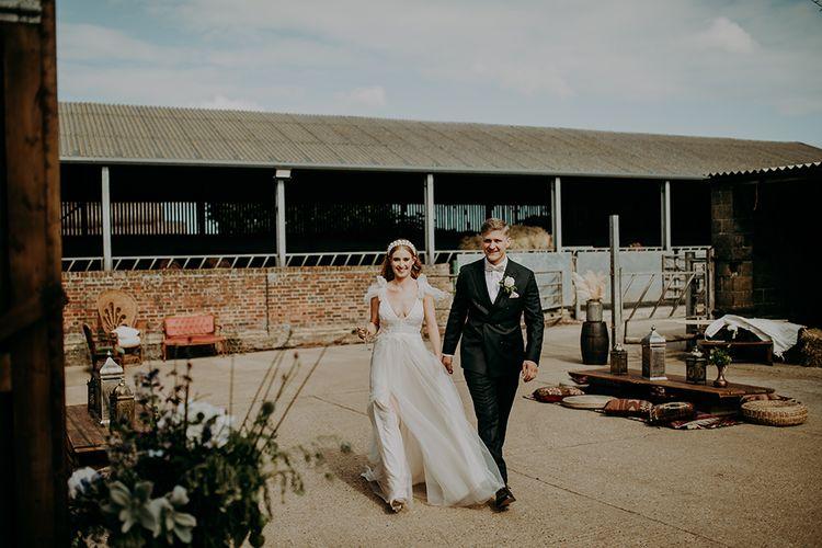 Bride in Inbal Dror wedding dress at rustic barn wedding reception