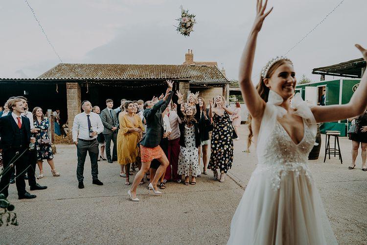 Bride in Inbal Dror wedding dress throwing her bouquet
