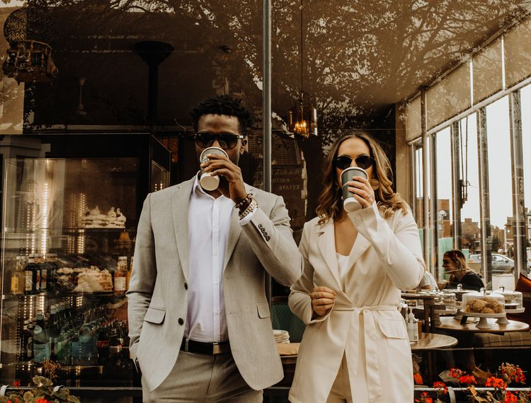 Bride and groom in sunglasses enjoying a coffee at city elopement