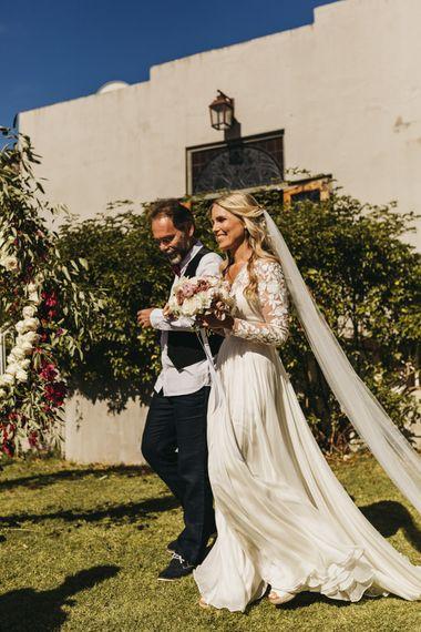 Bride in Catherine Deane wedding dress walks down the aisle