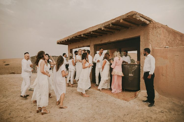 Wedding guests all dresses in white at desert wedding