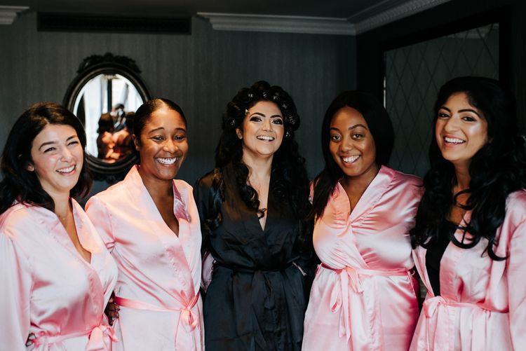 Bride and bridesmaids on the wedding morning in satin getting ready robes