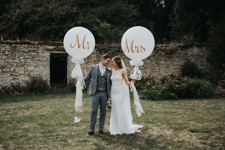 Bride and groom holding giant Mr & Mrs balloons with tassels