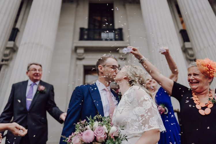Confetti moment for bride and groom before they step onto London wedding bus