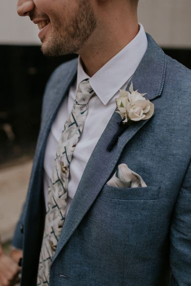 Groom in Blue suit and floral tie with white buttonhole