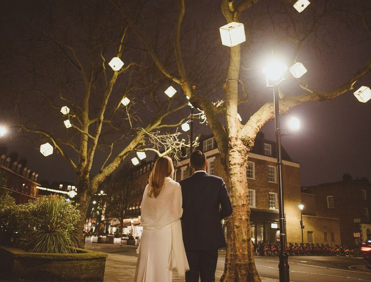 Bride and groom walking into the night outdoor winter wedding photography