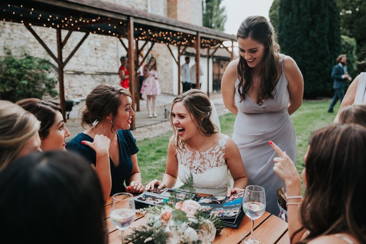 Bride laughing with friends at outdoor drinks reception