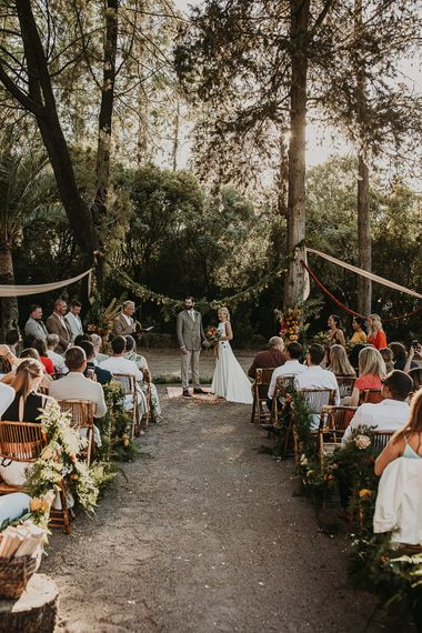 Forest wedding ceremony with wooden chairs and floral aisle flowers