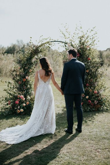 Bride and groom holding hands at outdoor wedding ceremony with floral moon gate