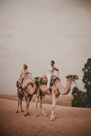 Bride and groom riding camels at Marrakech wedding