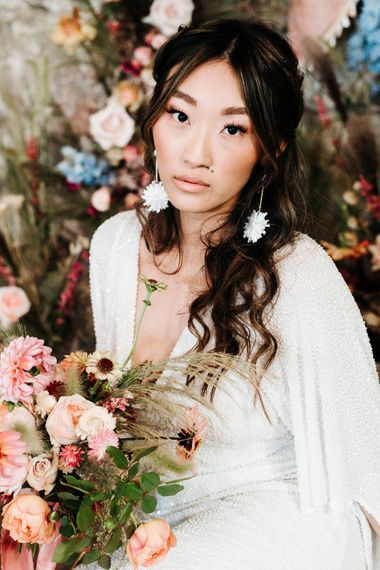 Asian bride wearing a sequin wedding dress and chandelier earrings