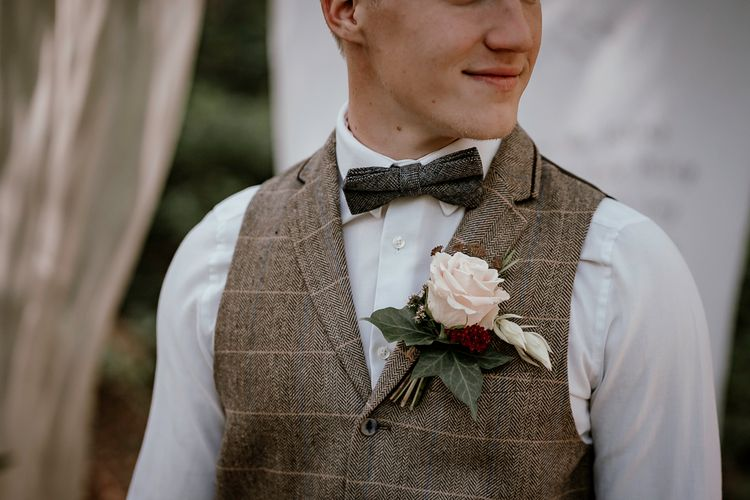 Groom in check waistcoat and bow tie at woodland wedding