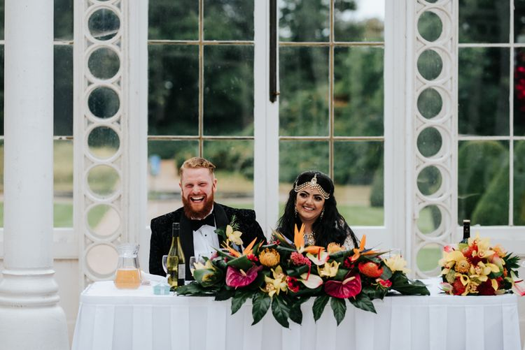 Sweetheart table with brightly coloured tropical plant floral decor