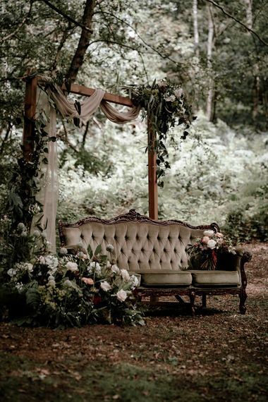 Vintage couch in the woods with locally sourced flowers