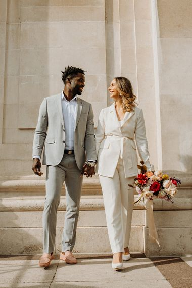 Stylish bride and groom in grey and ivory suits with colourful fashion and footwear