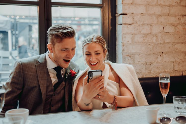 新郎新娘正在阅读不能参加他们微婚礼的宾客发来的信息