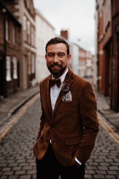 Stylish groom in cord jacket and bow tie at micro wedding