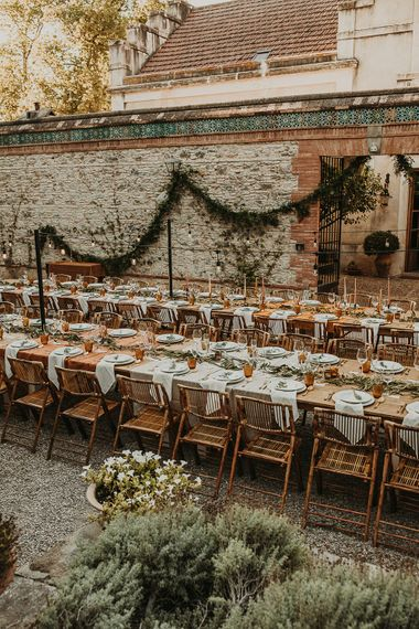 Wooden banquet tables decorated with foliage and earthy toned linens and candles