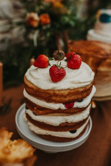 Stacked naked wedding cake with fruit topper