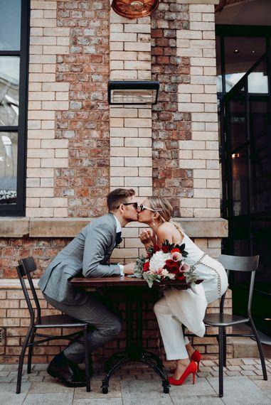 穿着马西莫·杜蒂连衣裤的新娘隔着桌子亲吻她的新郎