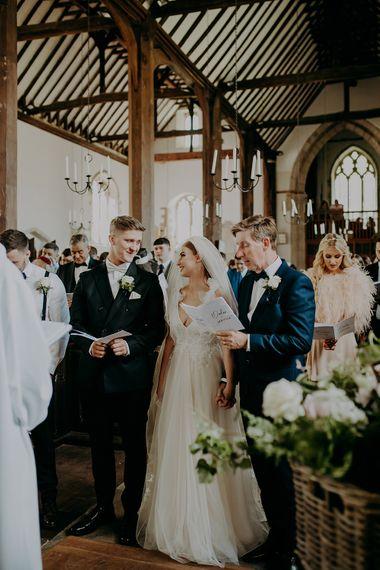 Bride in Inbal Dror wedding dress and groom in navy suit standing at the altar
