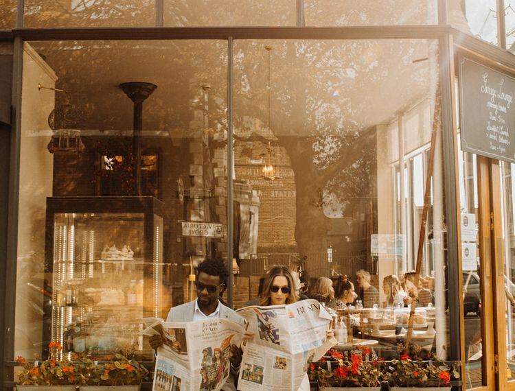 Bride and groom reading newspapers at city elopement