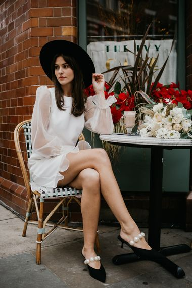 Bride sitting at a cafe in knee length wedding dress and fedora hat