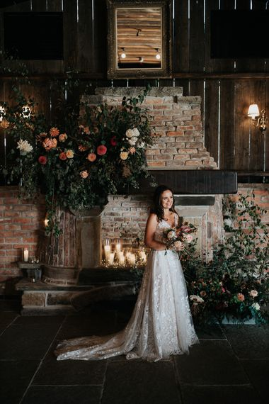 Bride in lace wedding dress standing in front of the fireplace decorated with flowers