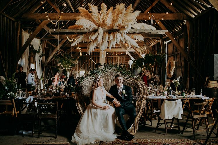 Bride and groom sitting on a peacock chair made for two under a pampas grass installation