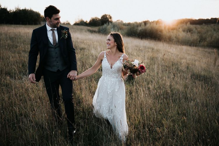 Bride and groom walking through the fields at Willow Marsh Farm