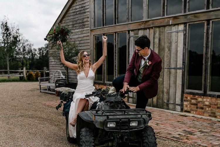 Bride in satin wedding dress and groom in burgundy blazer